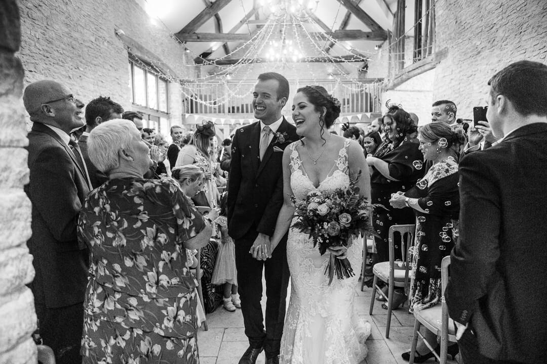 Bride and groom leaving wedding ceremony in Tetbury