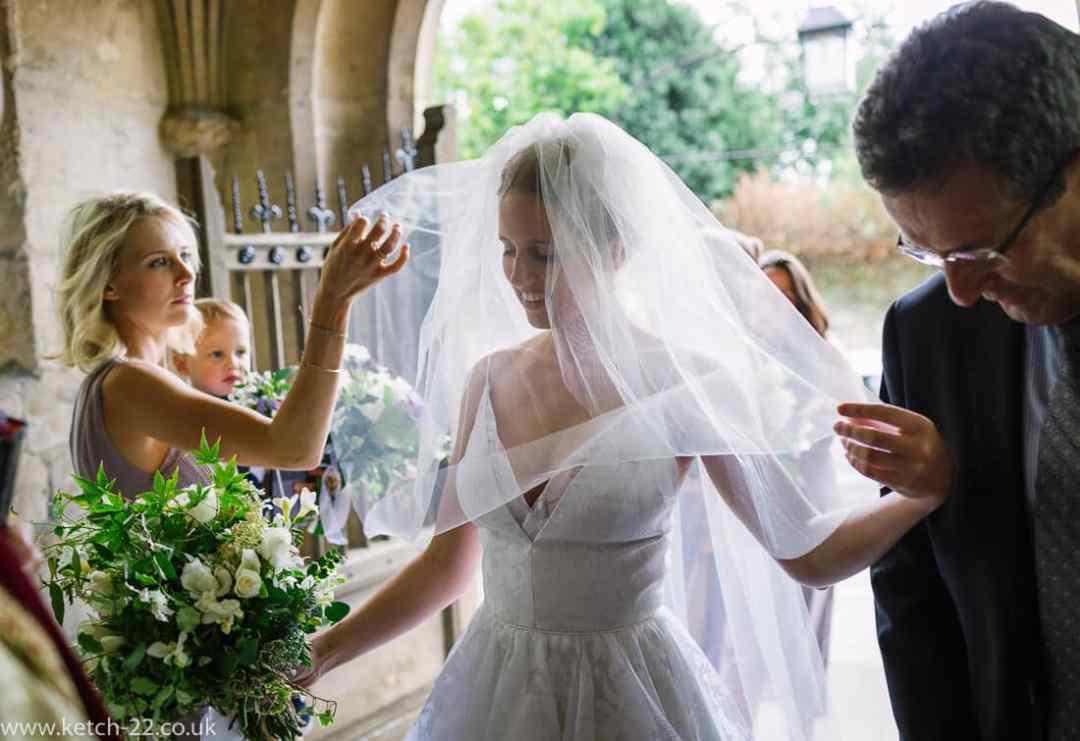 Bride having her veil adjusted - Wedding photographer Winchcombe
