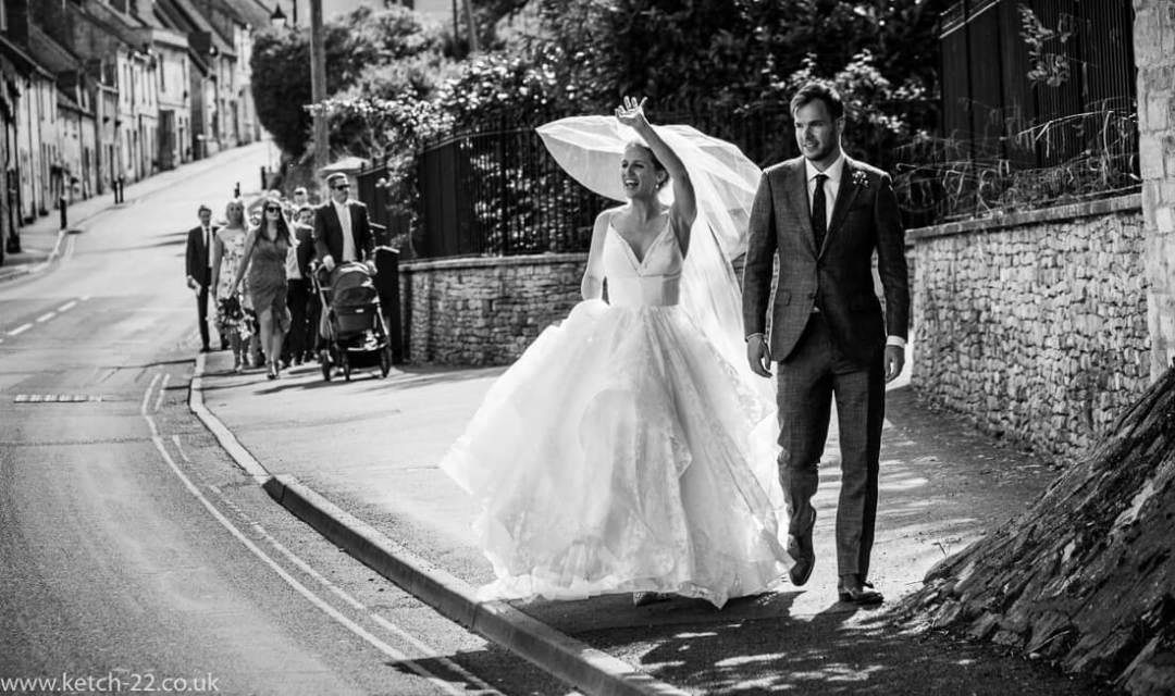 Bride waving to people - Winchcombe wedding photographer