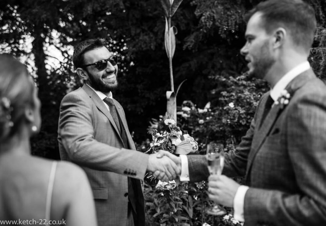 Groom greets his friend at Winchcombe wedding