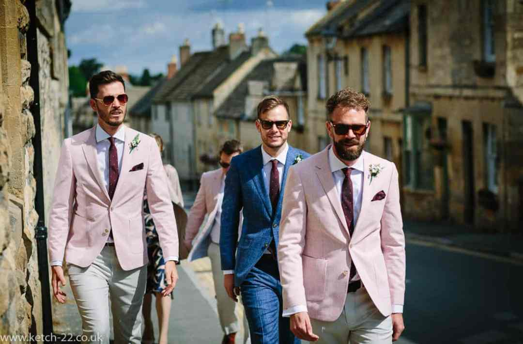 Groom in blue and best men in pink at wedding
