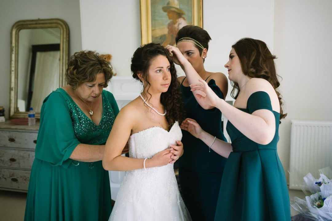 Bridesmaids and mum making a fuss over bride putting on wedding dress