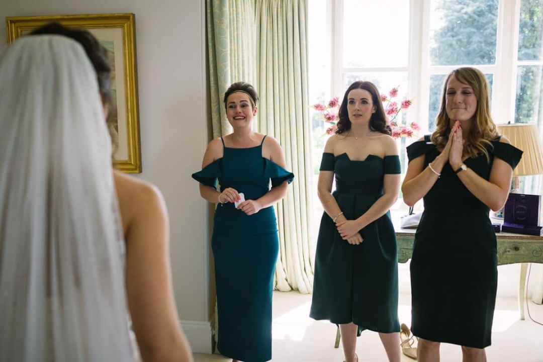 Bridesmaids looking at bride as she shows her Wedding dress off