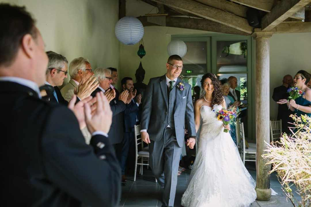 Bride and groom leave wedding ceremony
