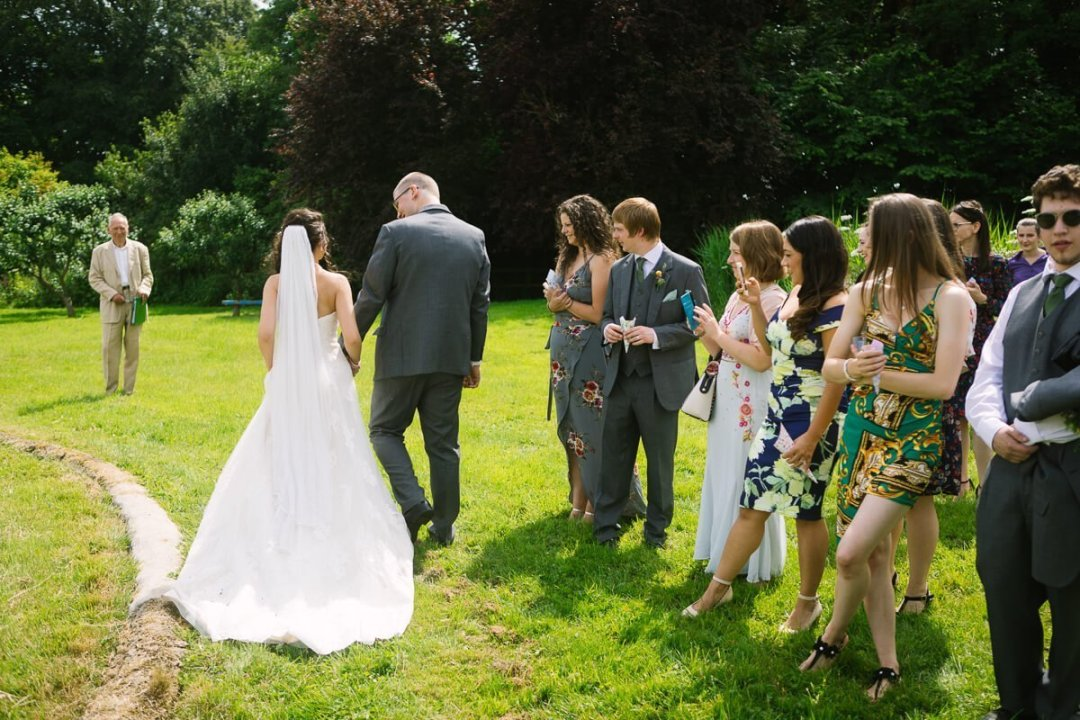 Bride and groom get applause from wedding guests
