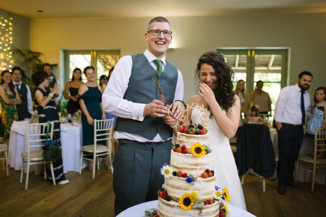 Newly weds cut wedding cake decorated with sun flowers and strawberries