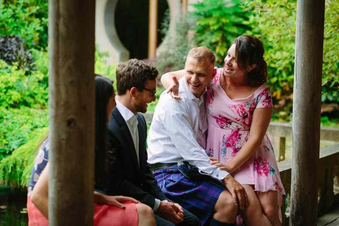 Wedding guest sitting on boyfriends lap