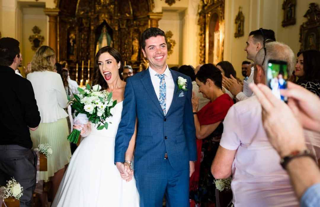 Bride and groom exit church at wedding in Spain