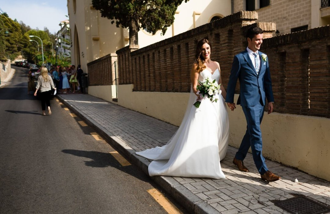 Bride and groom walking away from church at Wedding in Malaga Spain