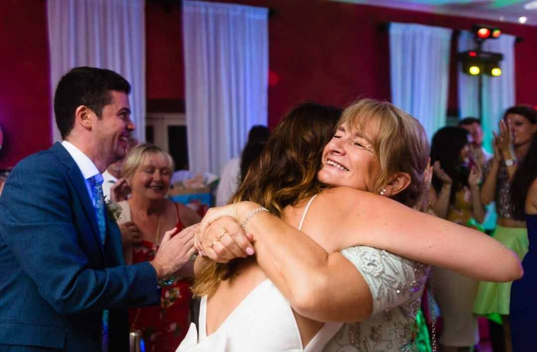 Mother of bride gives her daughter a big hug at Castillo de Santa Catalina Wedding in Spain