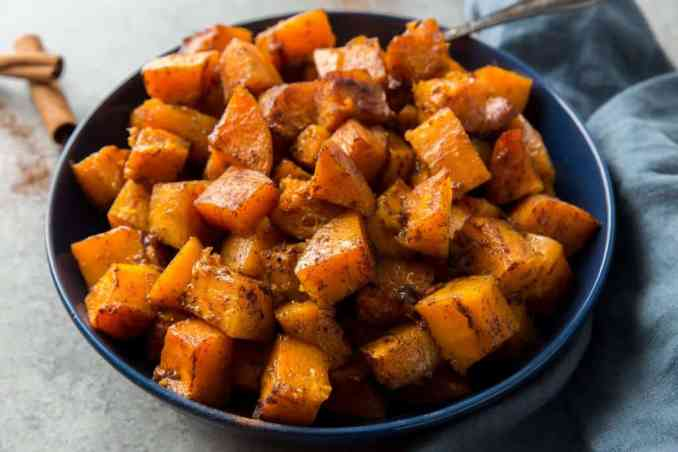 Finished butternut squash ready to serve in a blue bowl with a silver spoon
