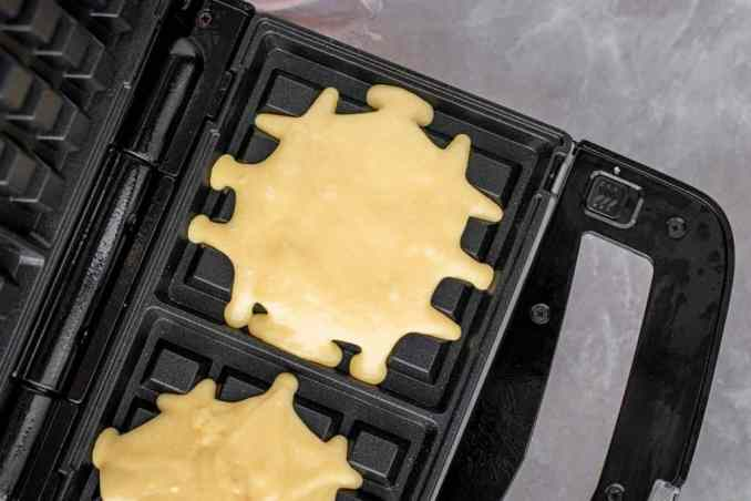 A waffle iron heating with two servings of raw batter to make waffles.