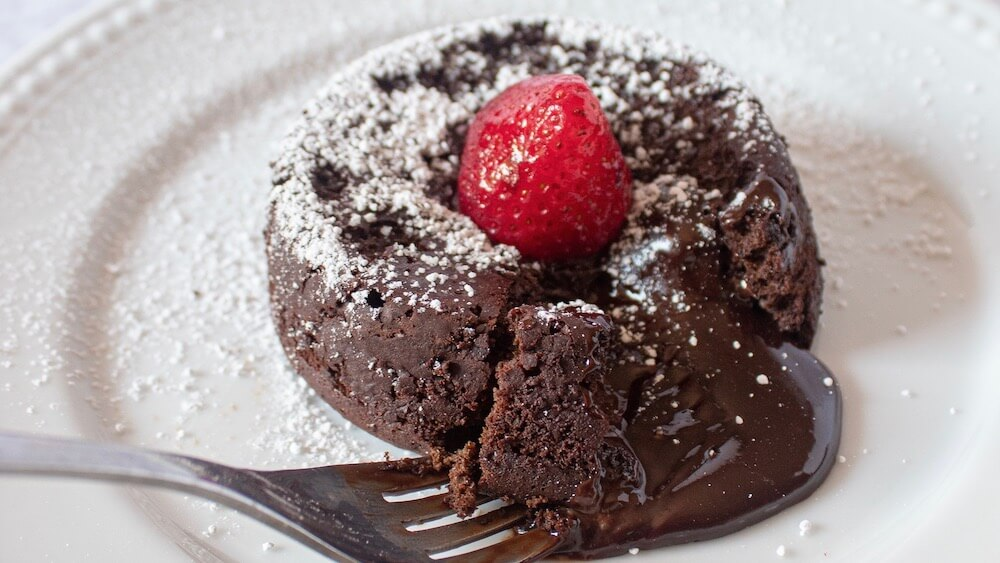 The best keto lava cake with fork taking a bite.