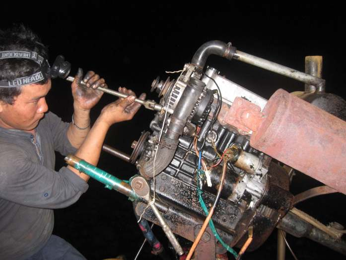 The small ship's captain drying to repair the boat motor in Cambodia – after dark, using my headlamp. ©KettiWilhelm2015