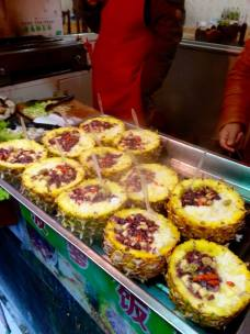 Cooked pineapples filled with rice and sweet bits of something. Wonderful, relatively safe treat in Jinan's snack street, Fu Rong Jie.