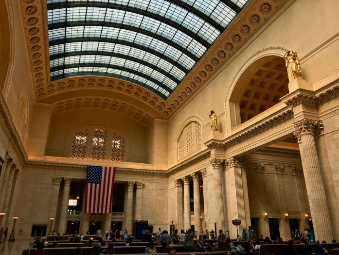 Towering columns and a US flag in the waiting room of Chicago's Union Station train depot, home to Amtrak passenger trains. ©KettiWilhelm2019