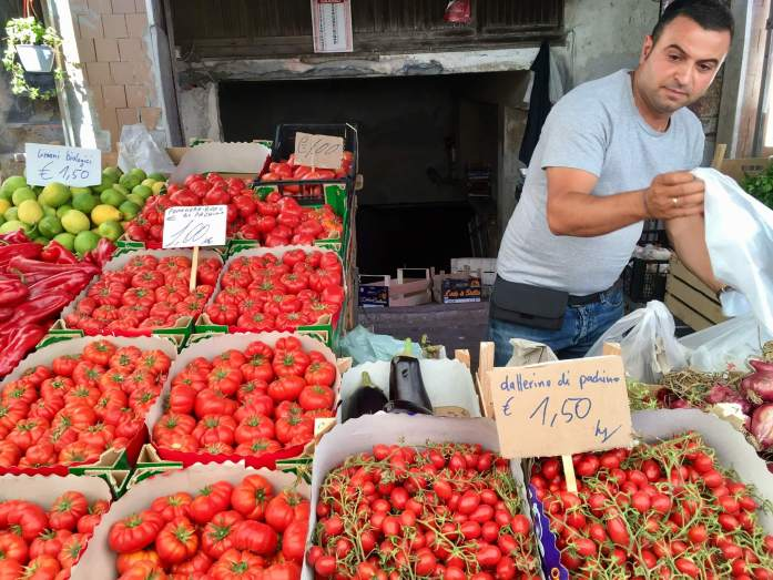 Many varieties of tomatoes and the man selling them at a vegetable market in Sicily. ©KettiWilhelm2017