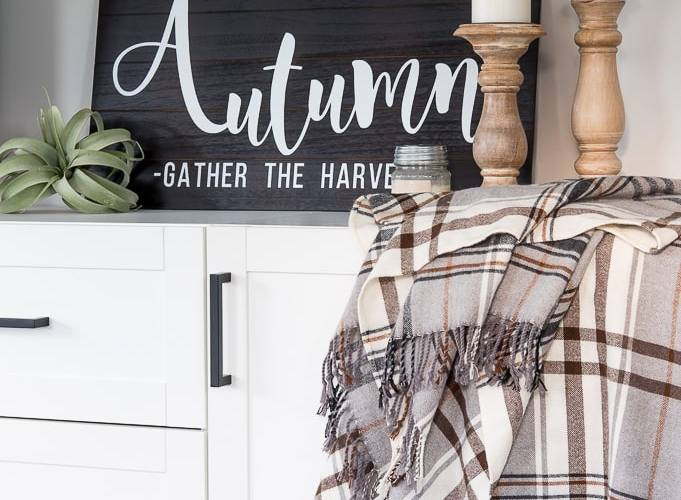 Wooden Autumn Hand-Lettered sign vignette on a media center with accessories
