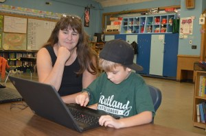 Student using computer with teacher