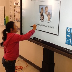 Student working on interactive whiteboard.