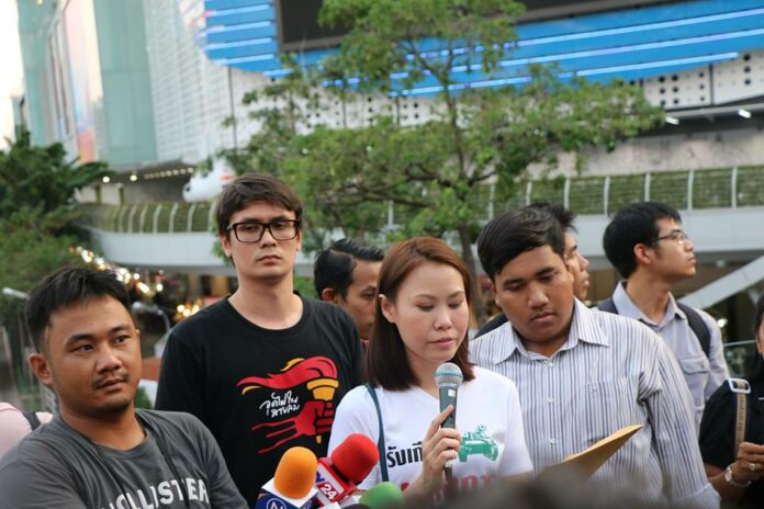 From left, an unidentified protest photographer, Rangsiman Rome, Nutta Mahattana and Sirawit Seritiwat at Saturday's protest on the Skywalk at Pathumwan intersection in Bangkok.
