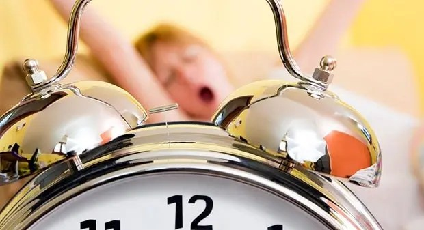Close up of alarm clock. Young woman in the background stretching arms above head and yawning.