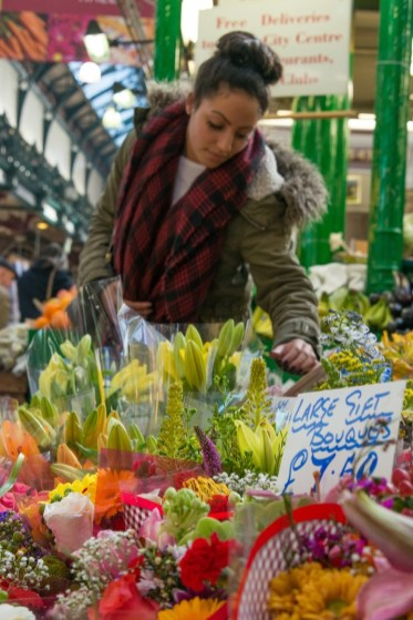 a girl choosing flowers in Leeds City Market