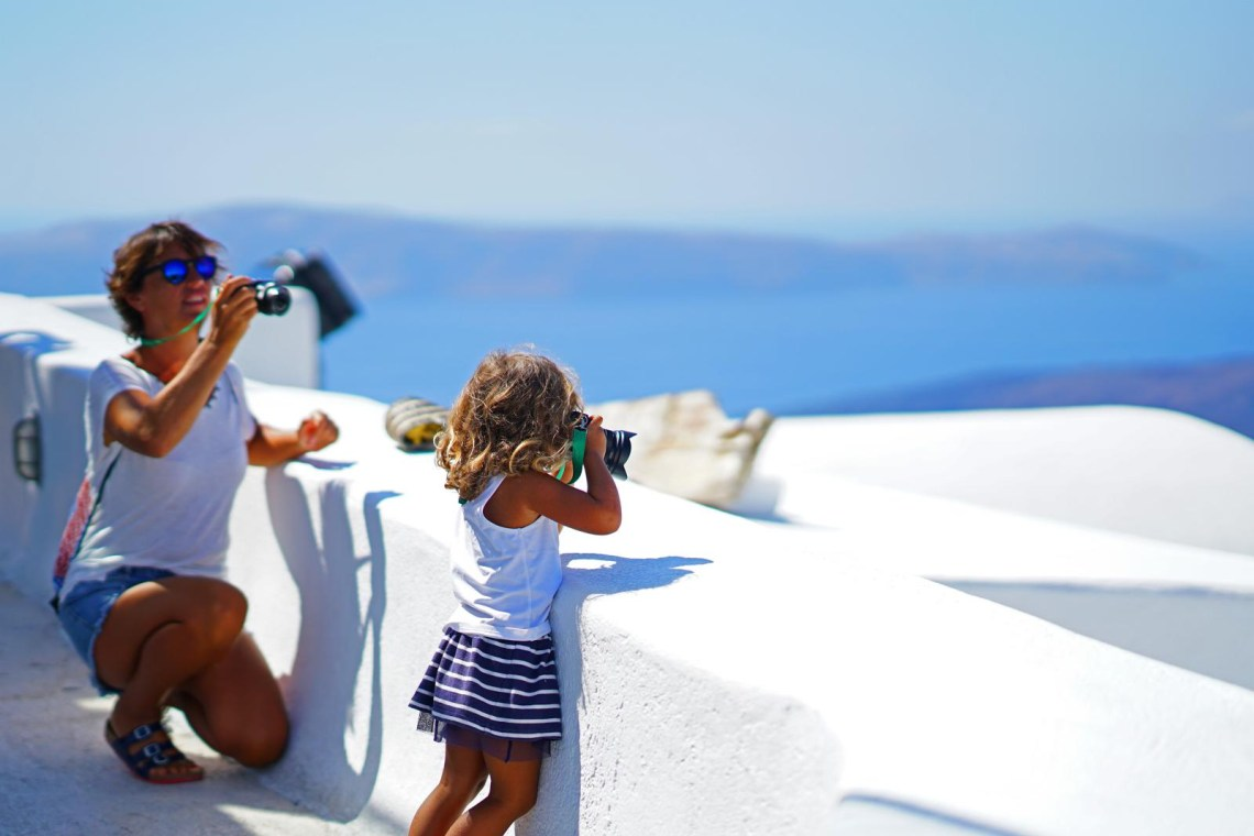 Mom taking picture of kid taking picture in Santorini KidsLoveGreece.com
