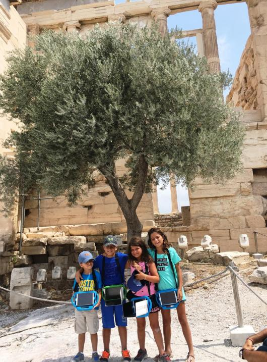 Kids with 3d virtual reality tablets infront of Parthenon
