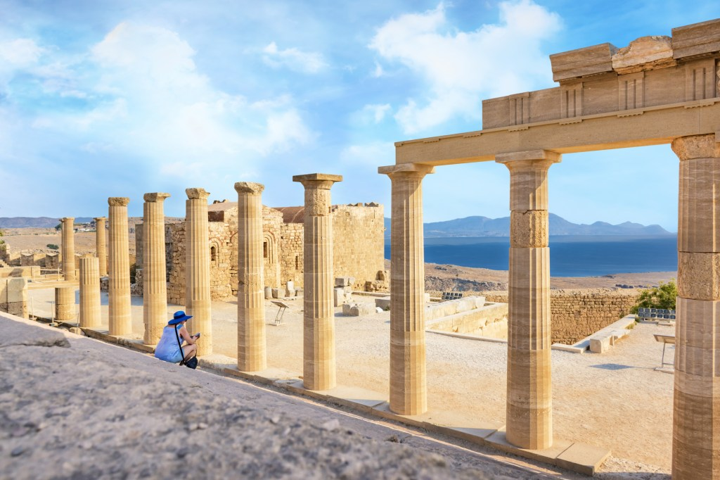 Woman sitting on Staircase of the Propylaea on the Acropolis of Lindos
