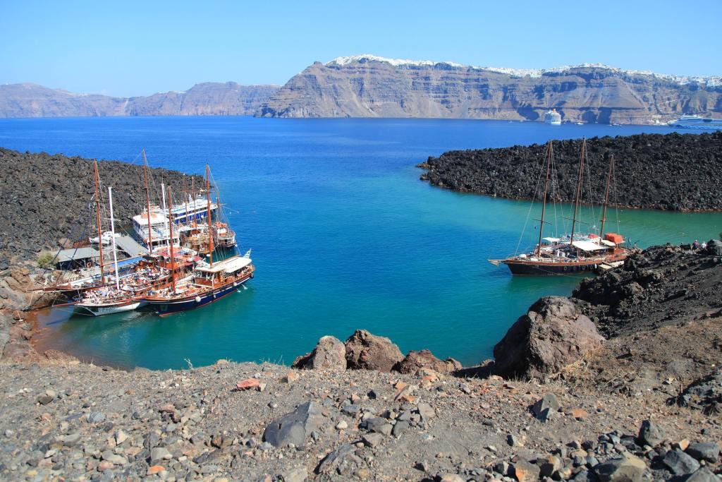 Tourist excursion boats at small port on volcano of Santorini SH-min