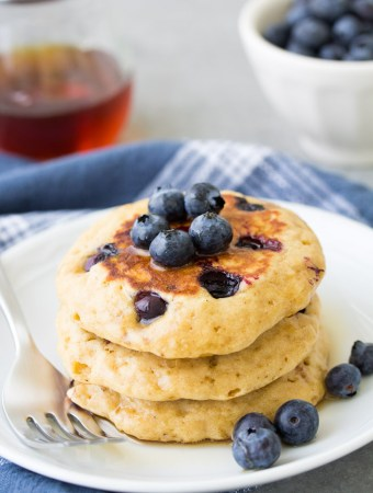 Healthy blueberry pancakes stacked on a plate with maple syrup and blueberries.