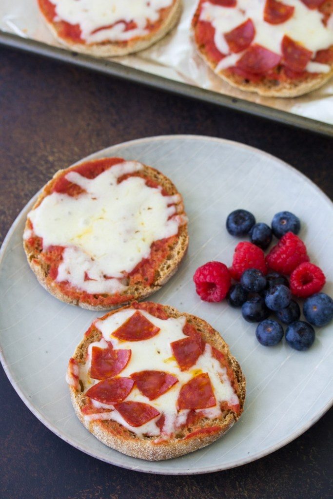 English muffin pizzas on a plate, served with berries.