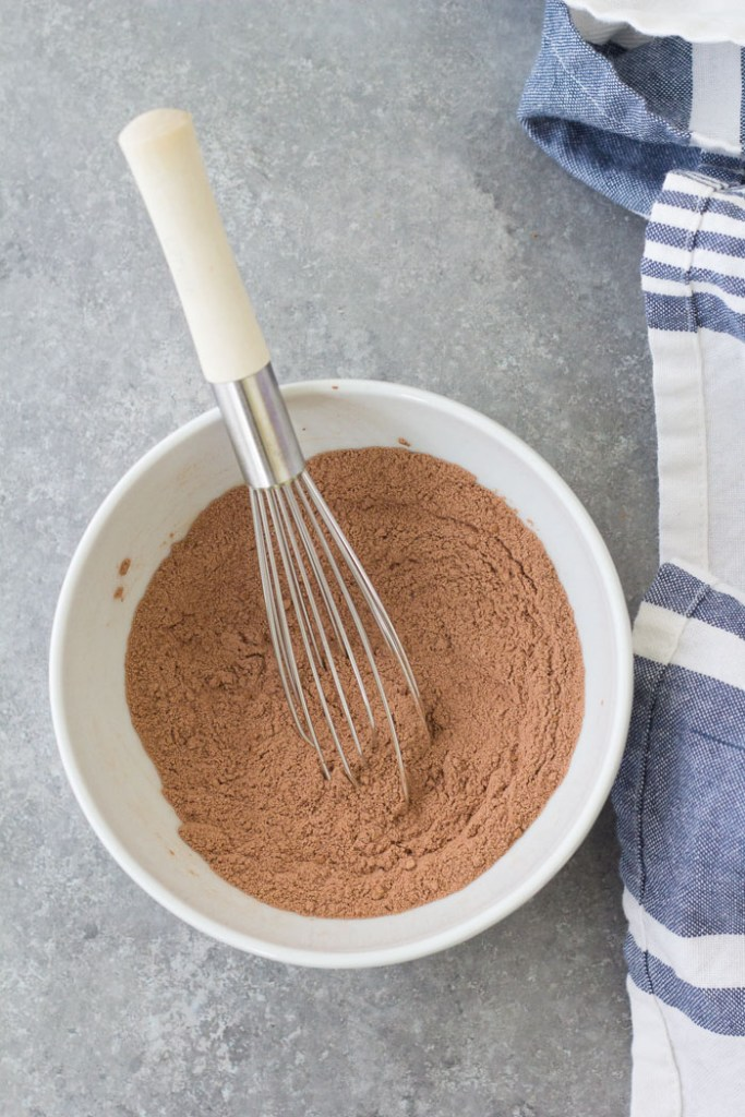 Whisking dry ingredients in a bowl for a chocolate mug cake.