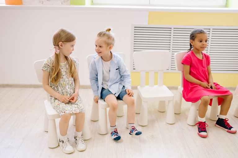 3 petites filles sont assises sur des chaises