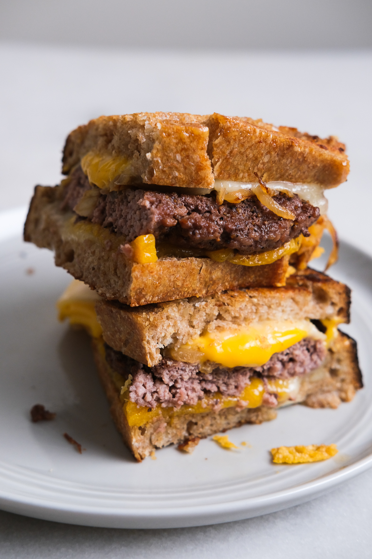 patty melt cut in half on a plate
