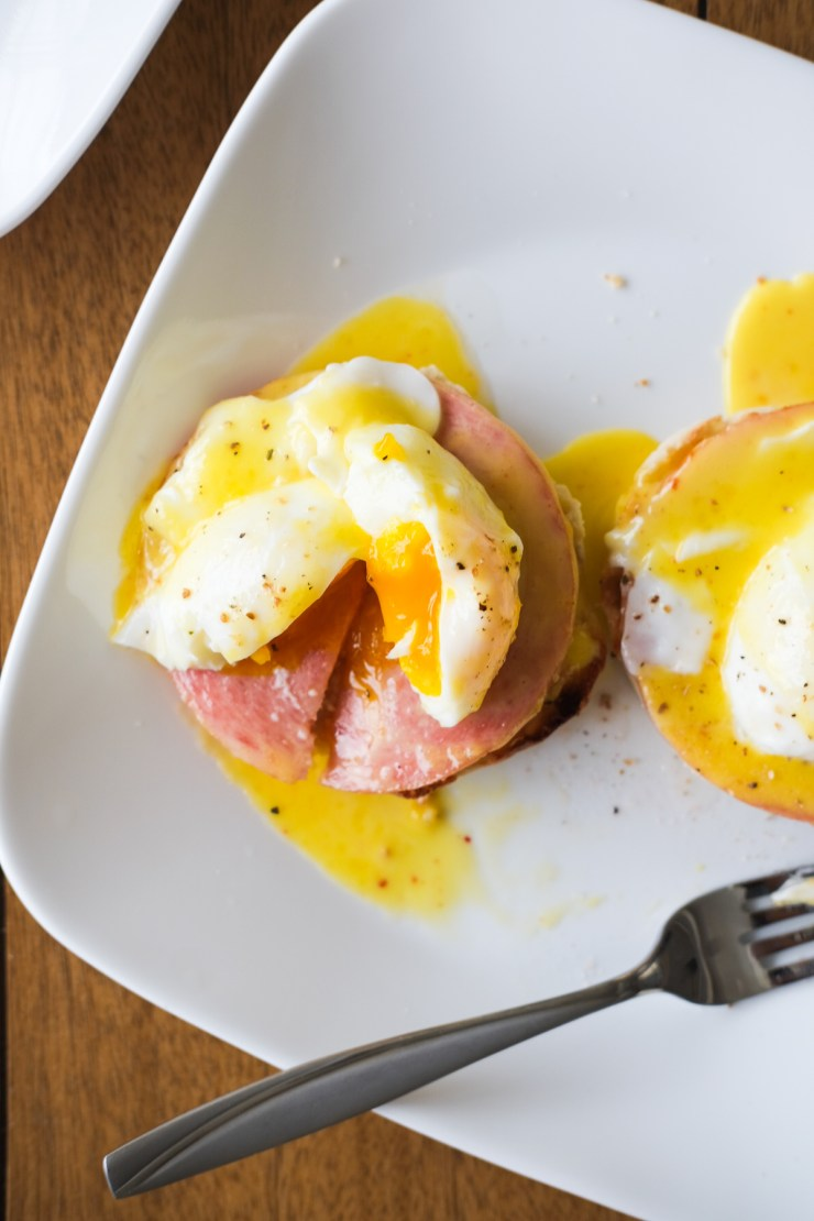 cut open eggs benedict on a plate