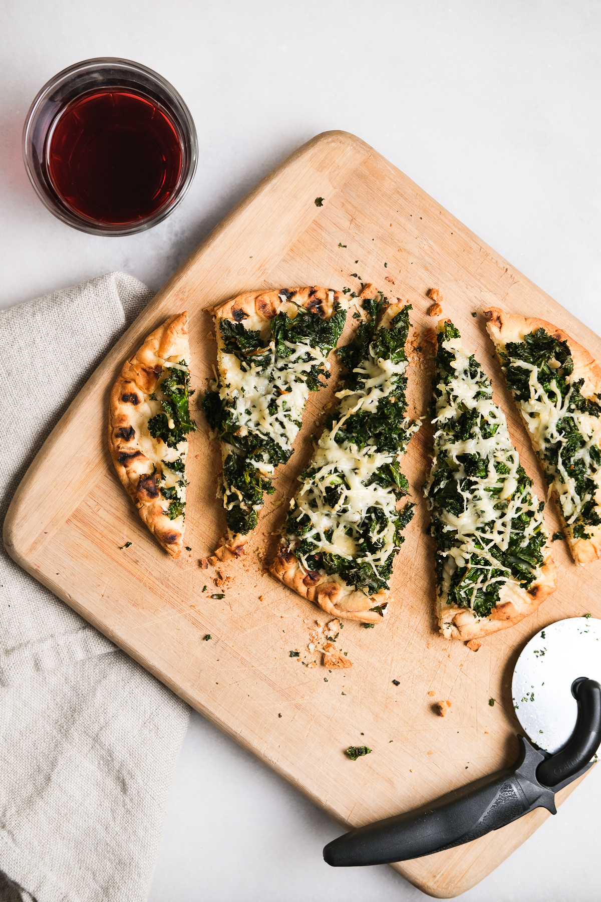 slices of kale parmesan flatbread pizza with wine