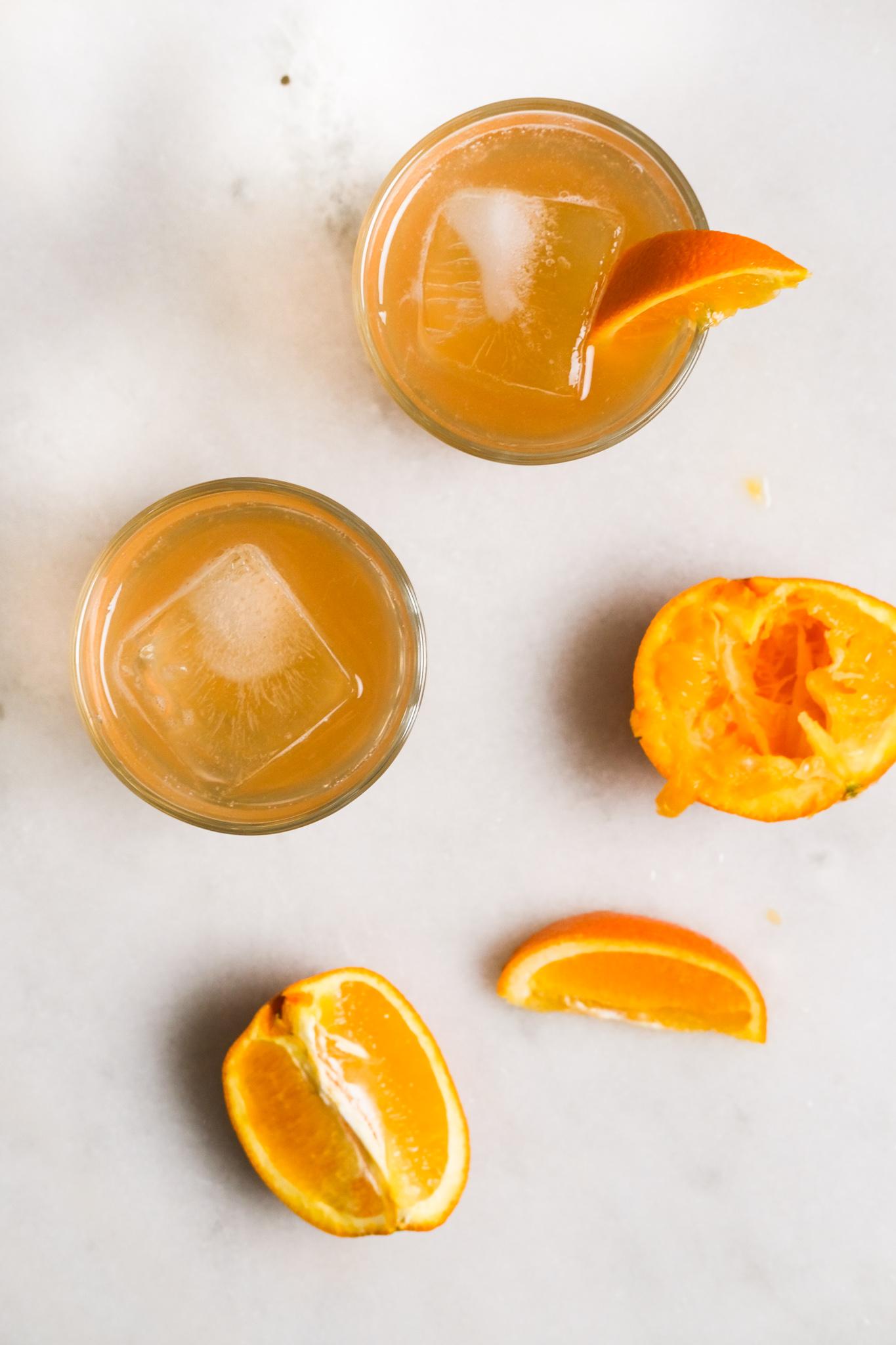 adding orange slices to orange cranberry bourbon cocktails