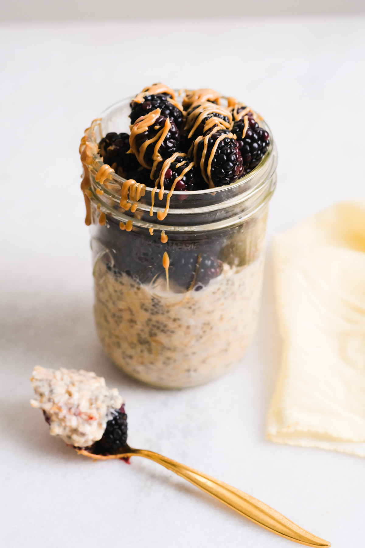 spoonful of peanut butter overnight oats with blackberries