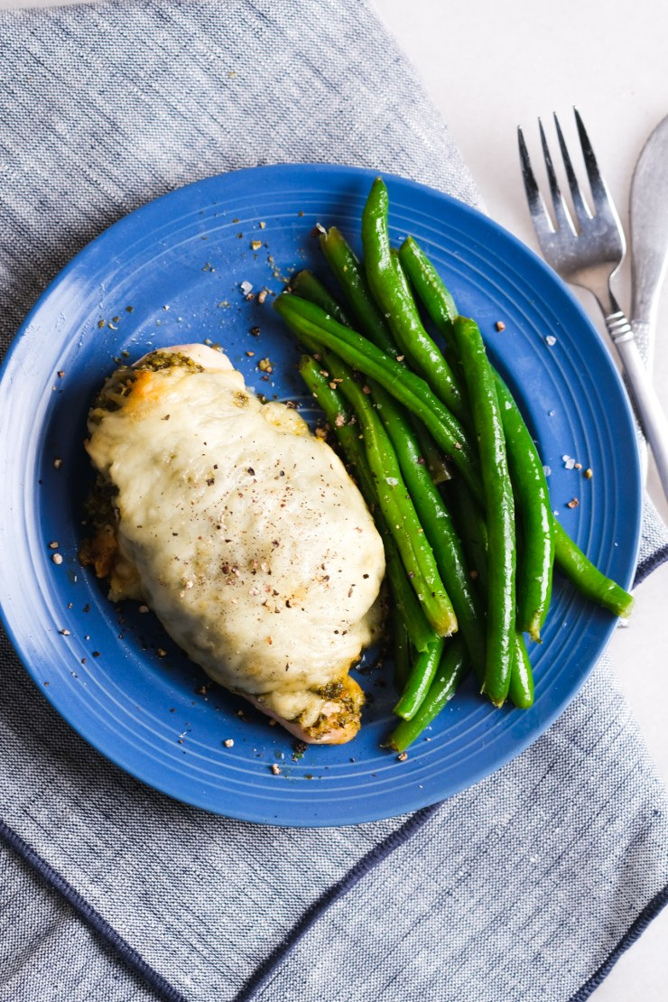 pesto chicken with green beans on a blue plate