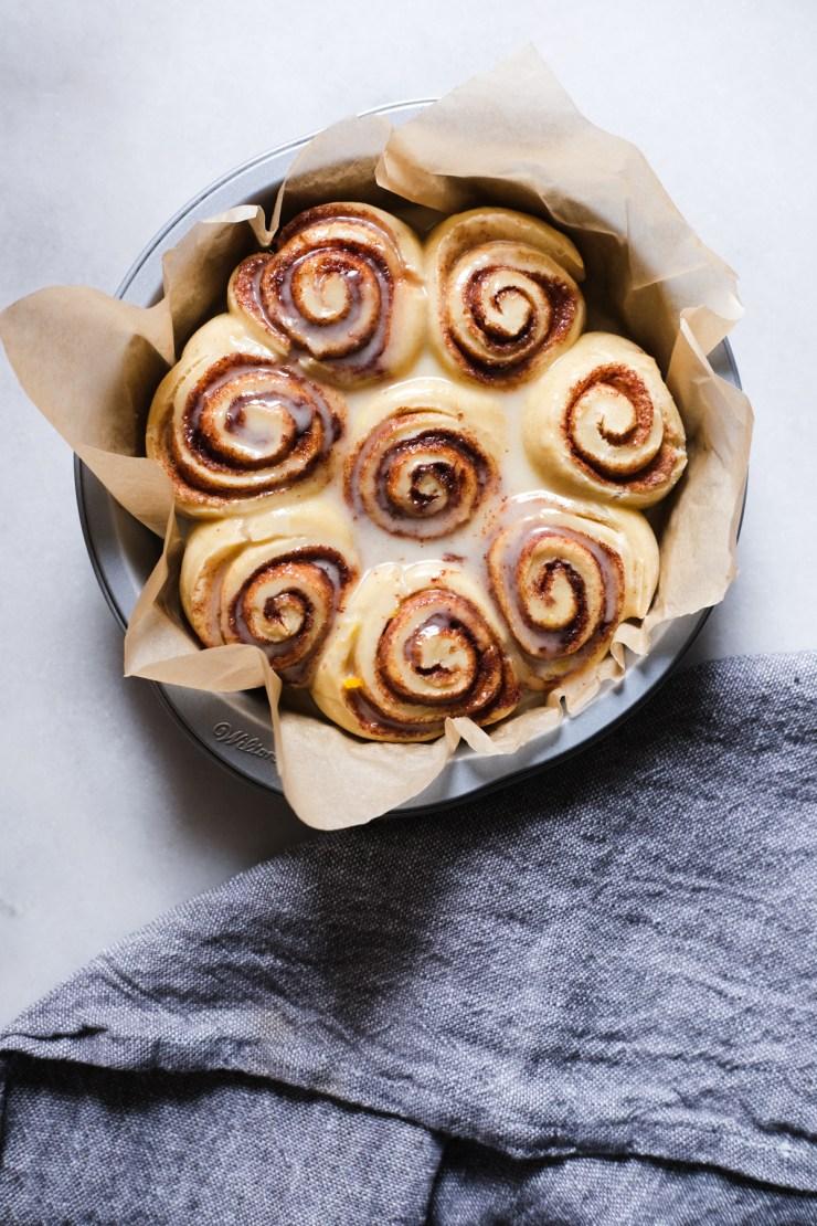 orange glaze on warm sourdough cinnamon rolls