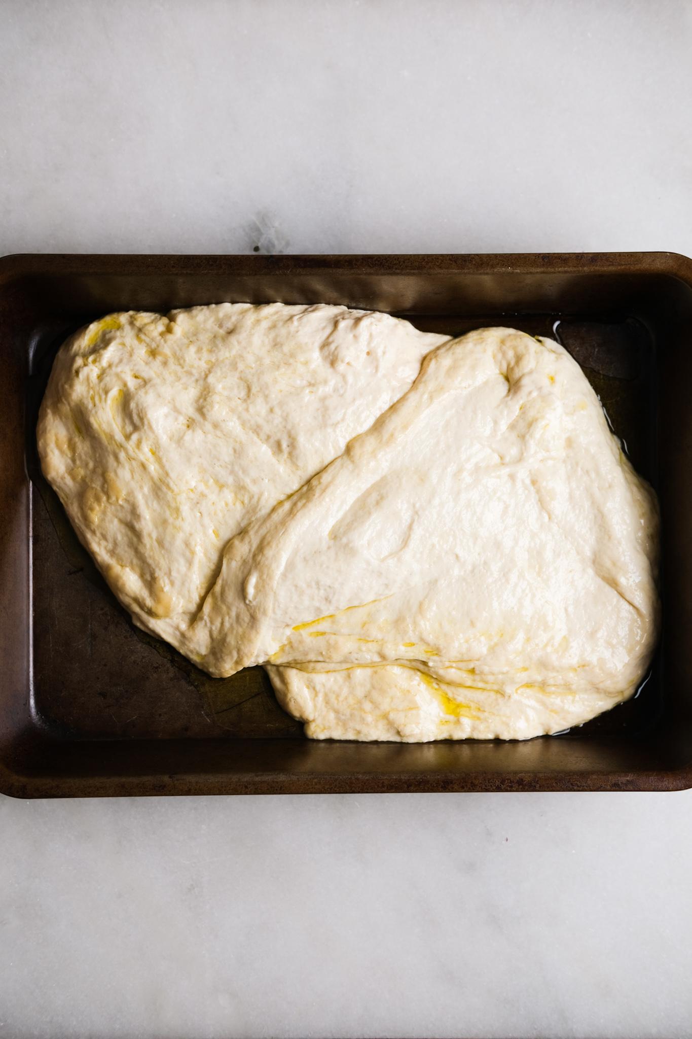adding focaccia dough to a baking sheet