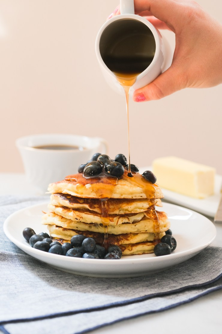 pouring maple syrup on a stack of blueberry lemon ricotta pancakes
