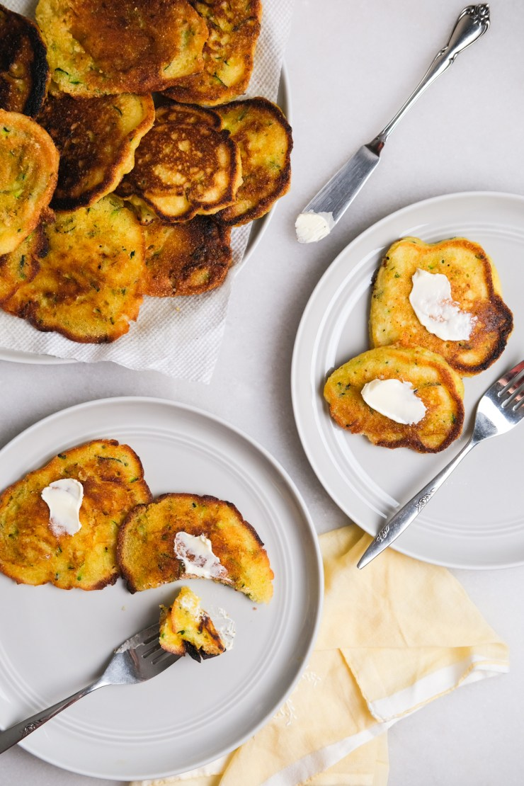 zucchini fritters on plates with spreadable butter