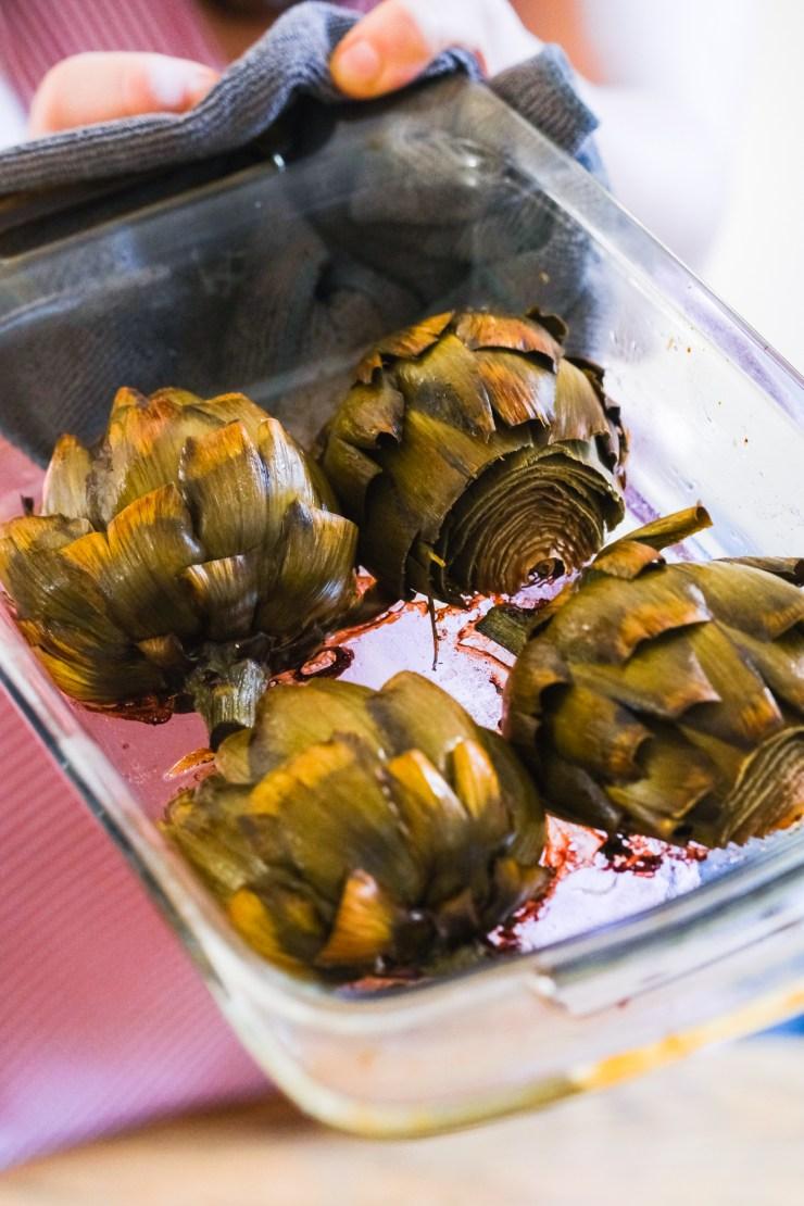 roasted artichokes in a glass casserole dish