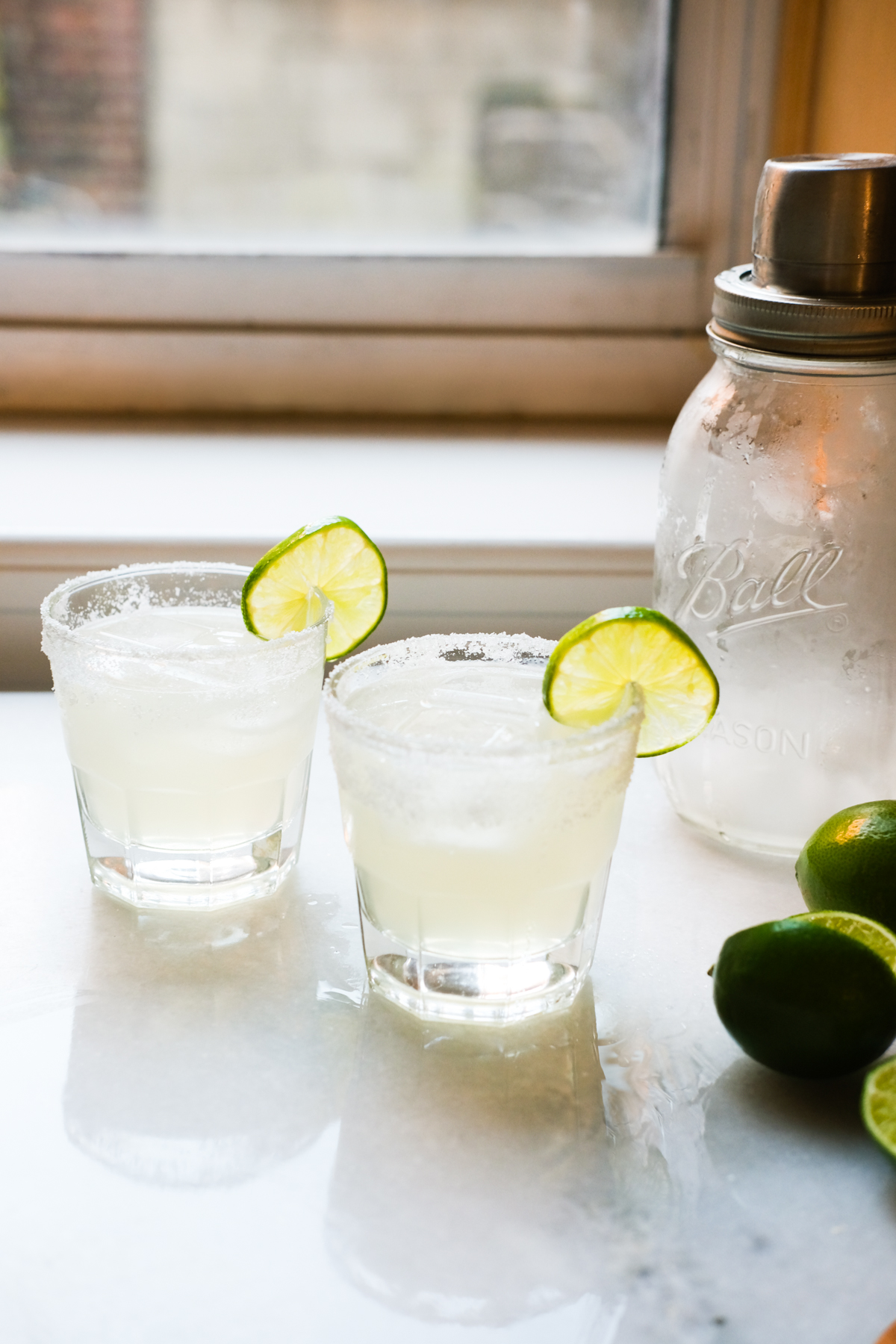 two margaritas with limes