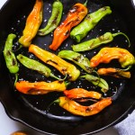 blistered shishito peppers in a cast iron skillet
