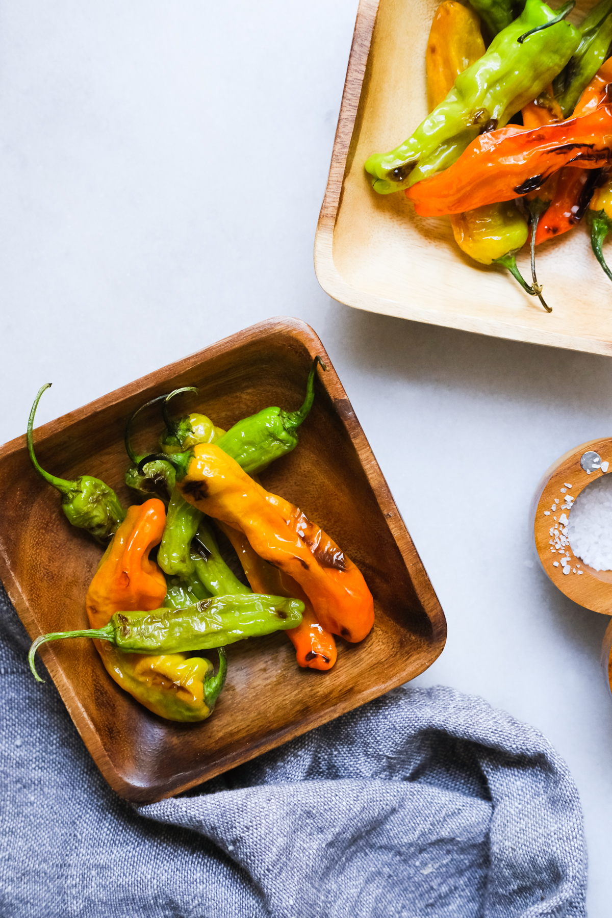 blistered shishito peppers in bowls with flaky sea salt