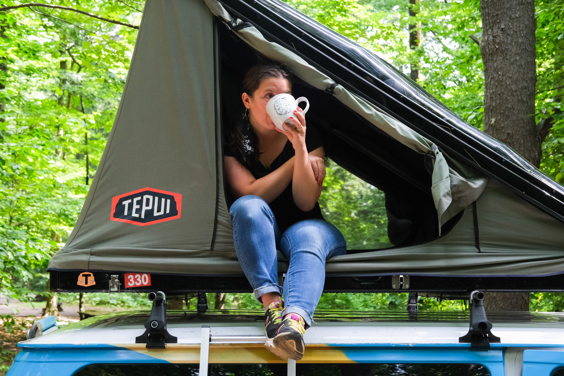 drinking coffee in a tent on top of a campervan